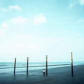Toddler standing alone on beach at low tide - Stock Image - C5186X