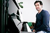 Man sitting at piano - Stock Image - CT3AN3