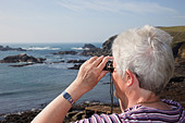 Lizard Point Cornwall England UK Senior woman looking out to sea through binoculars on coast at most southerly point of Britain - Stock Image - C82XHF