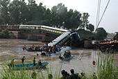 Gujranwala. 2nd July, 2015. Rescuers and local residents take part in a search operation after train compartments fell into a canal in east Pakistan's Gujranwala, July 2, 2015. At least 12 people were killed, over 100 others injured and at least four people went missing when four compartments of a train fell into a canal while crossing a bridge in Pakistan's city of Gujranwala on Thursday afternoon, local media and officials said. © Stringer/Xinhua/Alamy Live News - Stock Image - EWY44F