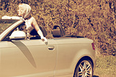 young woman leans out the open roof of a convertible - Stock Image - CP7F8T