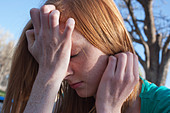 Close of a sixteen year old girl experiencing anxiety and covering her face with her hands outdoors. - Stock Image - CP0MGR