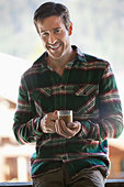 Portrait of smiling man drinking coffee - Stock Image - CWJKMC
