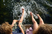 Children (6-7, 8-9)  sitting on pier with their feet splashing in the water - Stock Image - DWWRAG