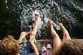 Children (6-7, 8-9)  sitting on pier with their feet splashing in the water - Stock Image - DWWRAG