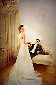 Full length of bride and groom in luxurious and with a vintage look interior with dress seen from the rear - Stock Image - BG8H6H