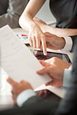 Executives reviewing document in meeting, cropped - Stock Image - EH9RMK