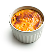 creme brulee in ceramic bowl on white background - Stock Image - CYH3MR