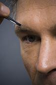 Closeup of man with tweezers plucking eyebrows - Stock Image - BJKGNG