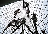 Vladivostok, Russia. 11th July, 2015. Participants grab onto netling during a Race of Heroes obstacle course event at the Gornostai testing range. © Yuri Smityuk/TASS/Alamy Live News - Stock Image - EXCA9E