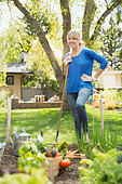 Portrait of woman with hoe in vegetable garden - Stock Image - E3RHXG