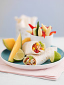 Prawn and vegetable wraps with melon wedges for lunch - Stock Image - BJHJA5