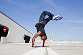 Man doing handstand on rooftop - Stock Image - CW04MM