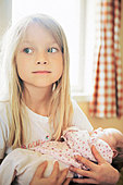 Close up of a girl carrying her sister - Stock Image - B50MWF