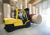 Fork lift carrying roll of paper - Stock Image - A04B9K