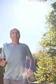 Senior man running outdoors - Stock Image - DFEJTM