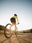 Mixed race woman riding on mountain bike - Stock Image - C8MHG3