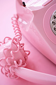 Cable wrapped around pink telephone receiver on pink background - Stock Image - AR3GM0