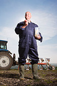 Farmer eating lunch in field with tractor and plough in background - Stock Image - BDHPRR