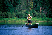 Man displays the art of poling a canoe. - Stock Image - AJ93HJ