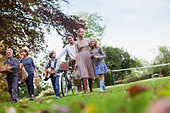 Multi-generation family with picnic baskets walking in park - Stock Image - CC9H1B