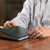 Older man holding book - Stock Image - CEFF61