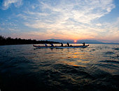 Five People Paddling a Outrigger Canoe on Lake Tahoe at Sunset, California - Stock Image - BA8H86