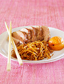Pork fillet with fried noodles and apricot - Stock Image - B487PN