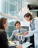 Waitress serving food to couple in restaurant - Stock Image - CWJPX9
