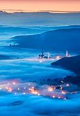 The Lafarge Cement Works & Lights of Castleton in Fog, Hope Valley, Peak District National Park, Derbyshire, England, UK - Stock Image - BTMGEE
