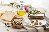 Lunch with green olives, bread and olive oil served with vintage book on old wooden table near window. - Stock Image - EAMWTK