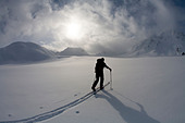 Backcountry skier crosses glacier under late day stormy sky. - Stock Image - BR14K0