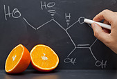 Hand drawing structural formula of vitamin C on blackboard with oranges in front - Stock Image - CFD06H