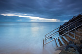 Waves washing over steps leading into sea.   Machans Beach, Cairns, Queensland, Australia - Stock Image - CMWX9D