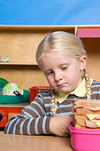 Girl looking at lunch box - Stock Image - BJRDK1