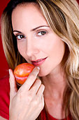 A mid adult woman eating a plum - Stock Image - BH6F33