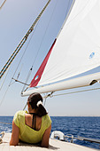 Woman lying on the deck of a yacht at sea, looking aft. - Stock Image - E46DCX