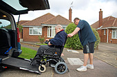 Male Carer son pushing a disabled elderly man in a wheelchair onto a built in ramp in a specially adapted car for getting about - Stock Image - CX7TD9