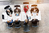 Overhead view of business team shaking hands with client at desk in office - Stock Image - EBHF5K