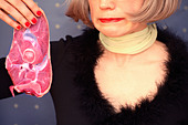 Woman holding a slice of raw meat with a look of disgust on her face - Stock Image - A3PK9W