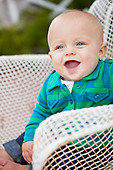 Laughing baby boy  with mouth open in wire chair, looking away - Stock Image - DX5H3P