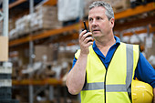 Man on walkie talkie in warehouse - Stock Image - CWAAYG