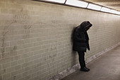 Hooded person leaning on subway wall - Stock Image - CR1H7D