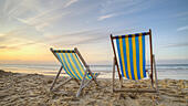 Two empty deck chairs on a beach at sunrise - Stock Image - D3X2KP