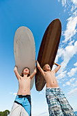 Spain, Mallorca, Children with surfboard on beach - Stock Image - CP64CX