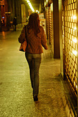 Italy, Milan, Lady walking down the street - Stock Image - AKJD10