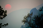 Sun setting through the thick atmosphere among the mountains of Laos. - Stock Image - BRRPKT