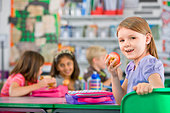 Smiling children eating lunch in classroom - Stock Image - BYB82P