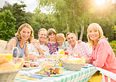 Multi-generation family enjoying lunch at table in backyard - Stock Image - DRCAFF