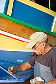 Man repainting a Luzzu_A Traditional Maltese foreign fishing boats - Stock Image - B0T17N